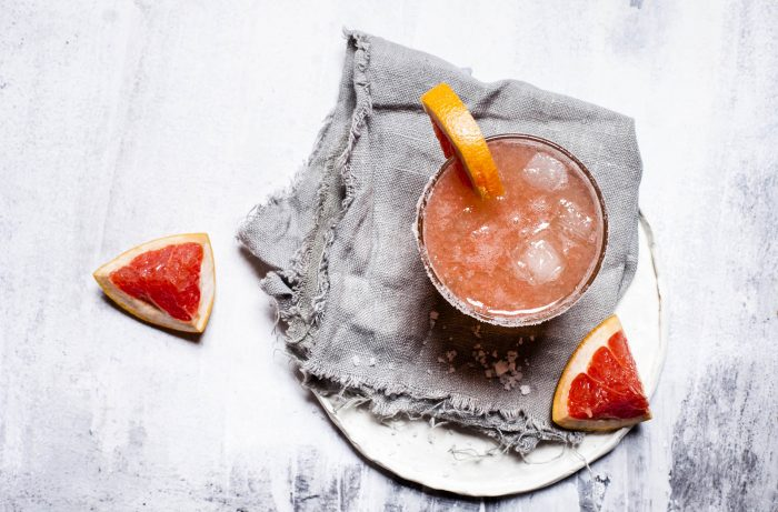 Top-down view of spicy paloma cocktail with grapefruit and habanero rim