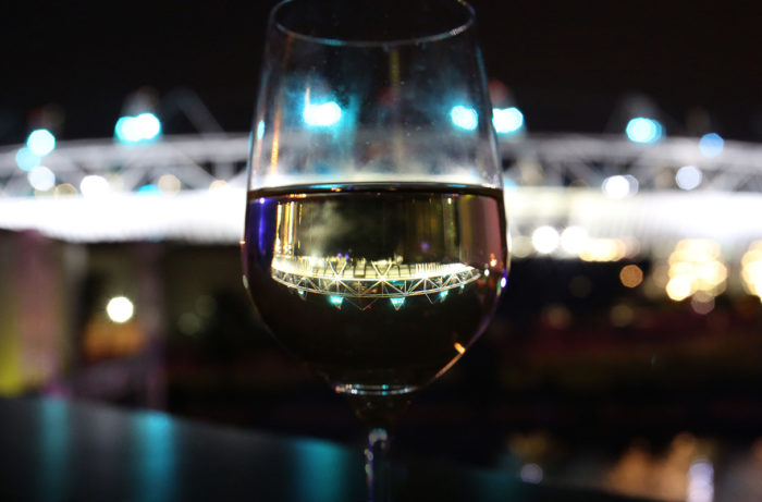 London Olympic stadium reflected through wine glass