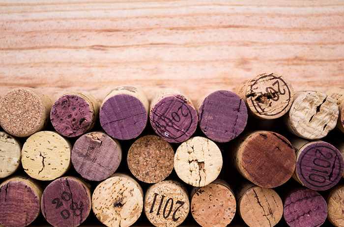 An array of wine corks on a wooden surface.