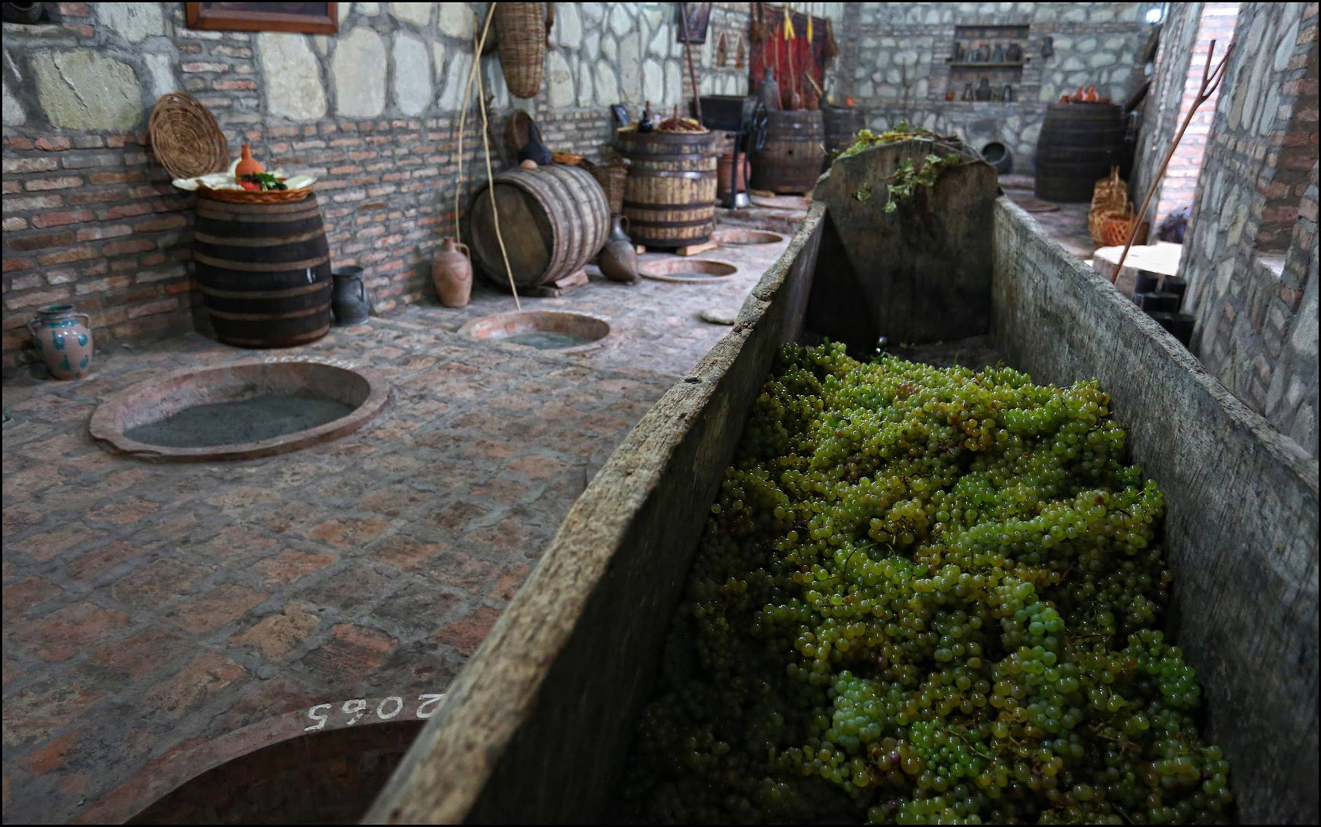 Georgian qvevri fully buried, alongside Rkatsiteli grapes destined for fermentation / Photo courtesy Wines of Georgia