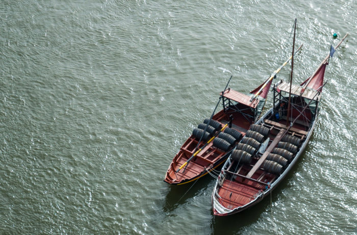 Wine barrels being transported down the Douro River by boat in Portugal / Getty