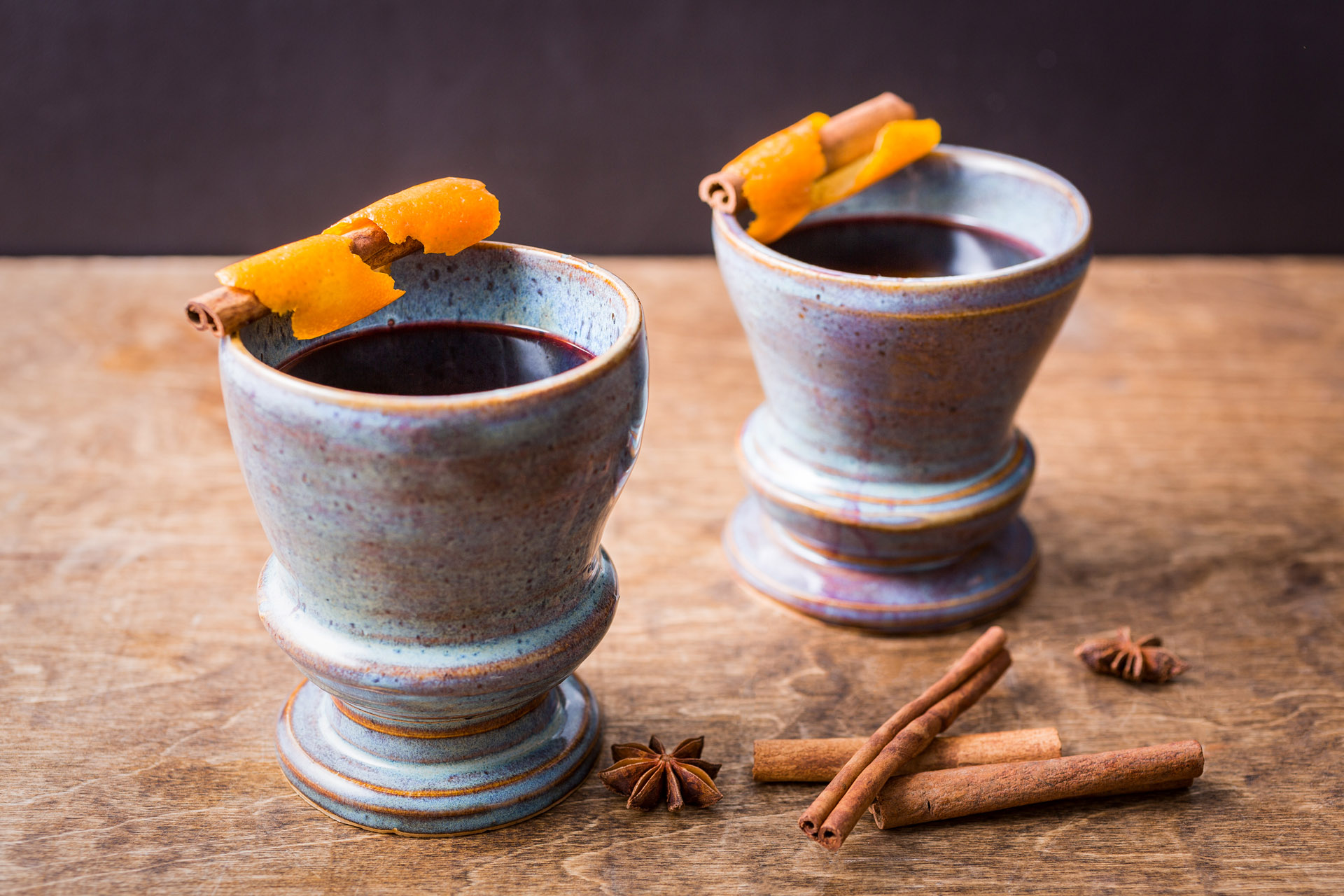 Two earthenware mugs filled with mulled wine and garnished with orange and cinnamon
