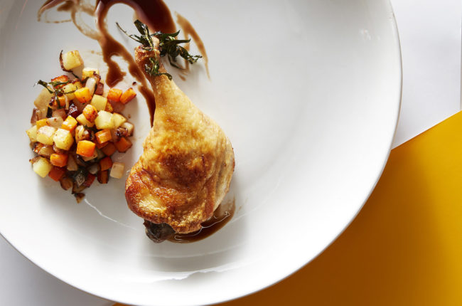 Duck legs with roasted vegetables and pomegranate jus.