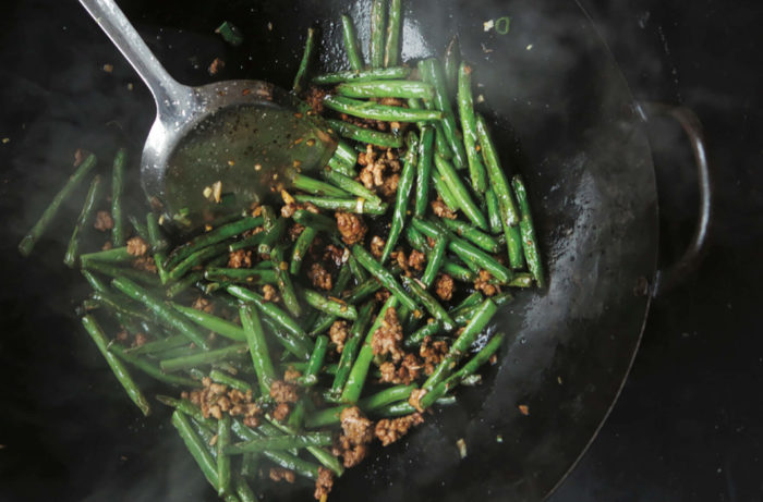 Dry-fried green beans with ground pork cooking in a wok.