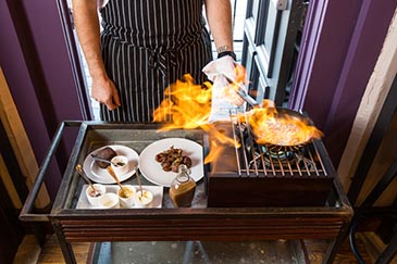 Food being cooked over an open flame at One Fifth