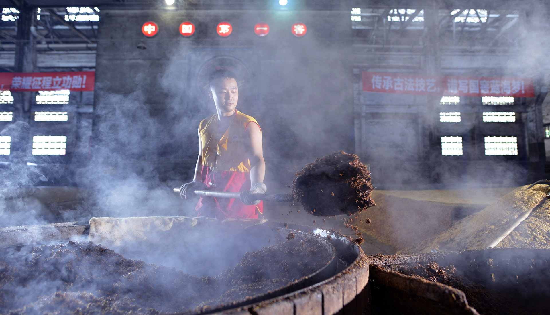 A portion of spent mash being removed from baijiu production to make room for fresh grain / Photo courtesy Luzhou Laojiao