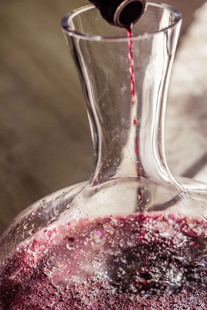 The last drops of a bottle of red wine being poured in a decanter to let it aerate.