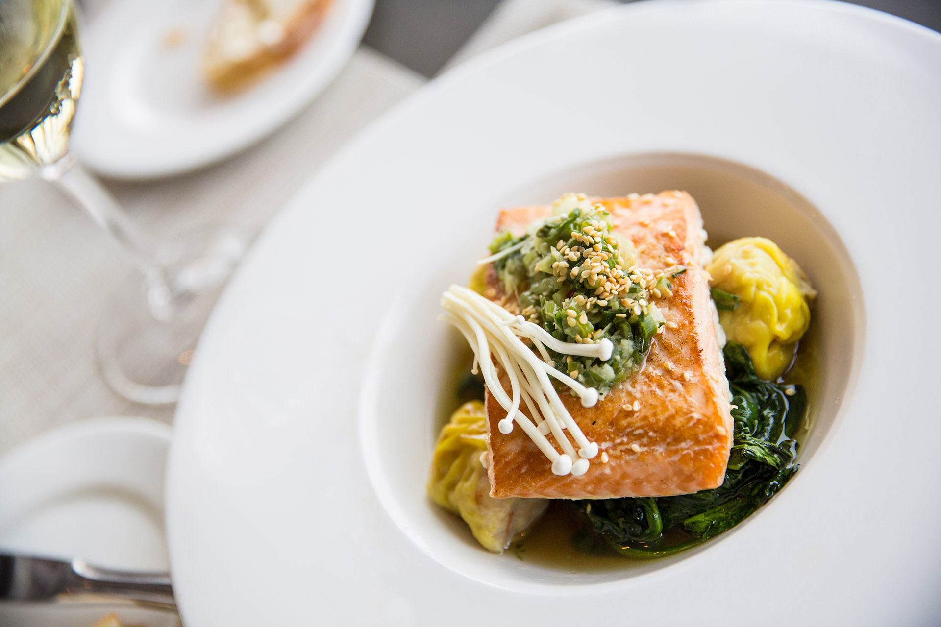 Pan seared Atlantic Salmon with spinach, toasted sesame seeds and enoki mushroom gourmet dinner paired with white wine