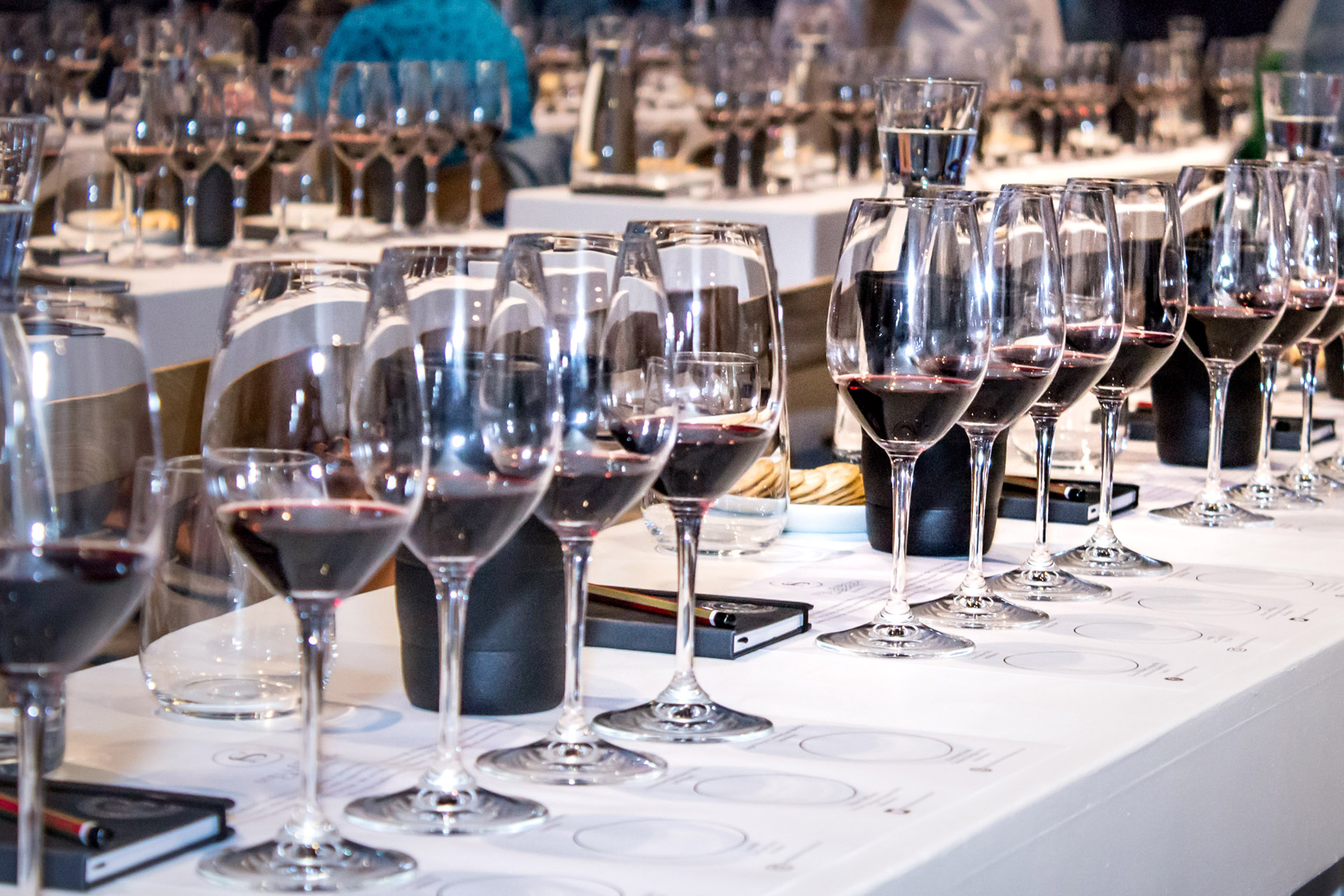 Line of wine glasses with deep red wine in them