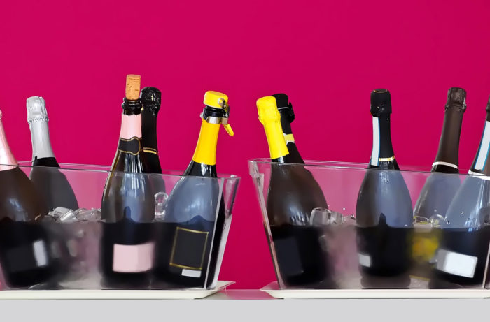 Sparkling wine bottles, some opened, in two transparent ice buckets at a wine tasting. Purple wall background