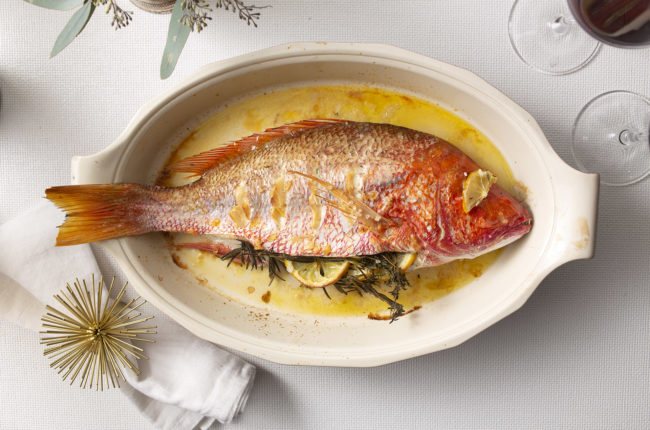 Whole baked red fish stuffed wtih herbs and lemon slices in an oval dish