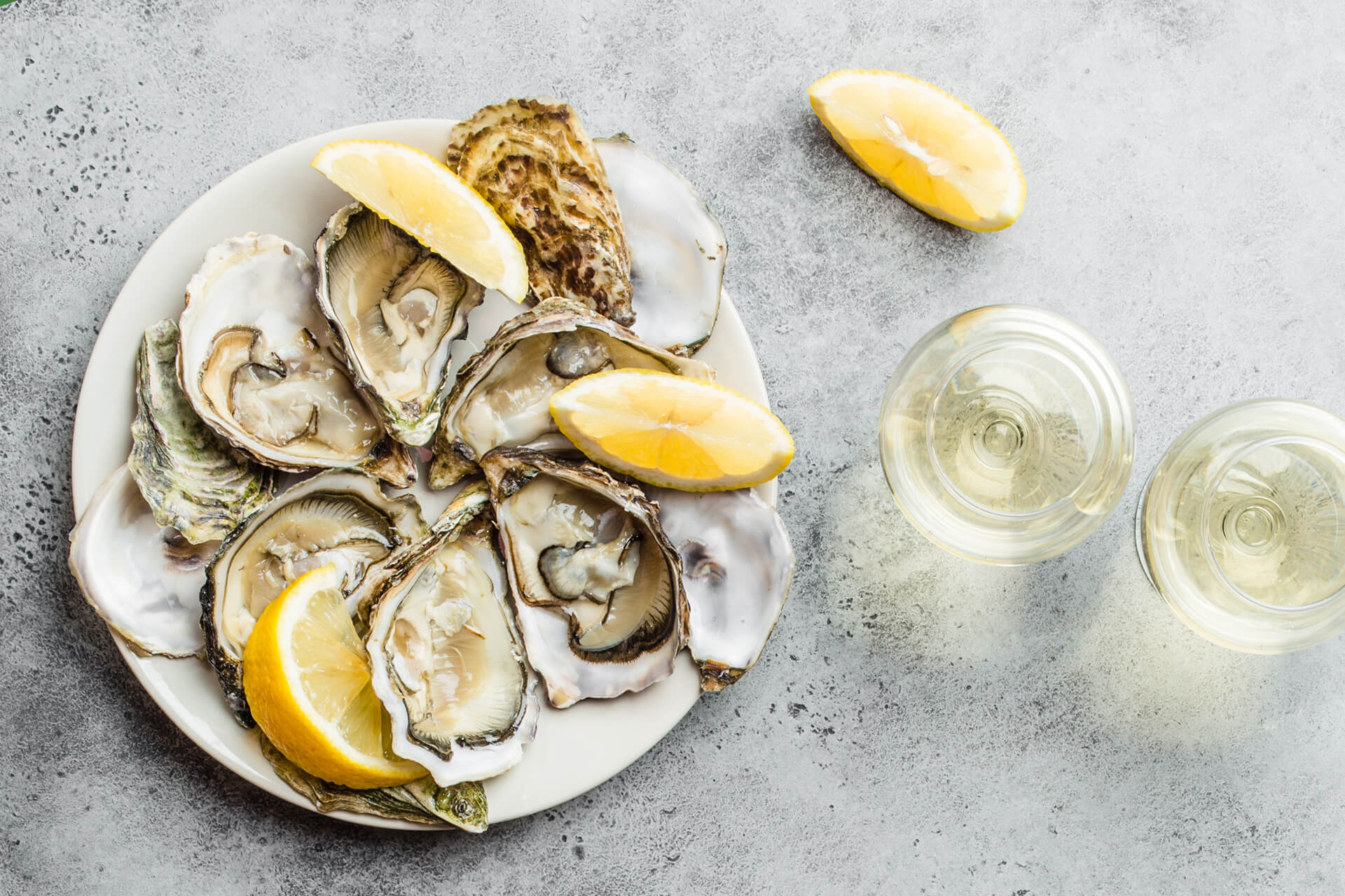 Close-up of half dozen of fresh opened oysters and shells with lemon wedges on a plate, two glasses of white wine, top view, grey rustic concrete background, space for text