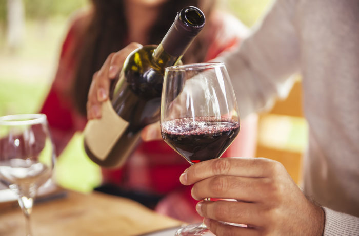 A photo of a man pouring red wine.