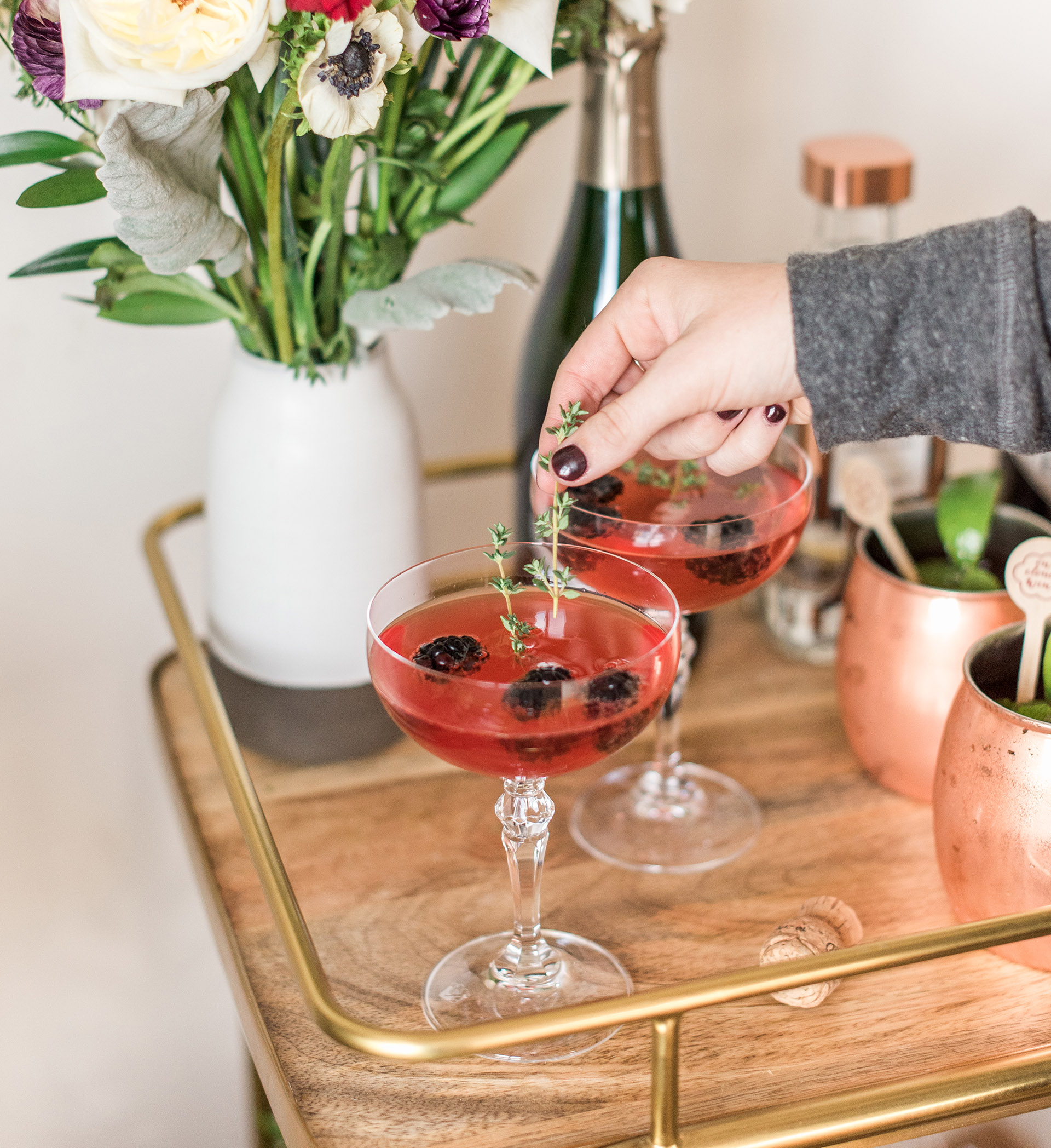 Two coupe glasses holding pink liquid and three blackberries on a bar cart