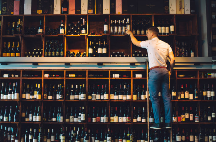 Man on a library ladder placing wine bottles on shelves
