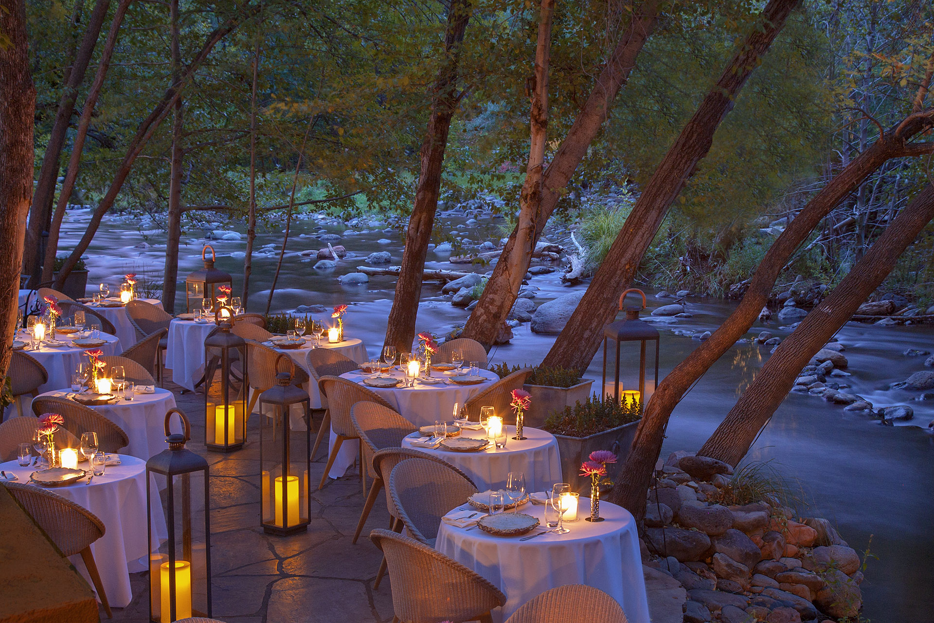 Candle-lit white tables set for dinner, large lit lanterns, all next to a creek with rounded rocks