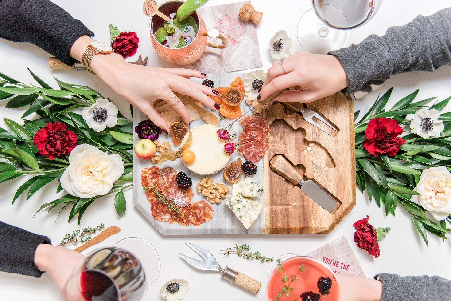 Bird's eye shot of a full cheese and charcuterie board, two people cutting into cheeses