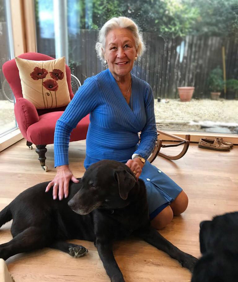Older woman in a blue dress, in a living space, kneeling with a large balck dog in front on her