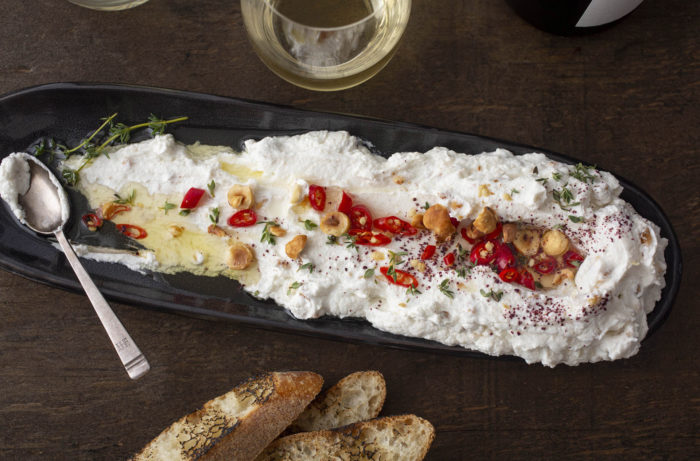 Labneh spread out on a platter, garnished wtih peppers and hazelnuts, crostini to the side