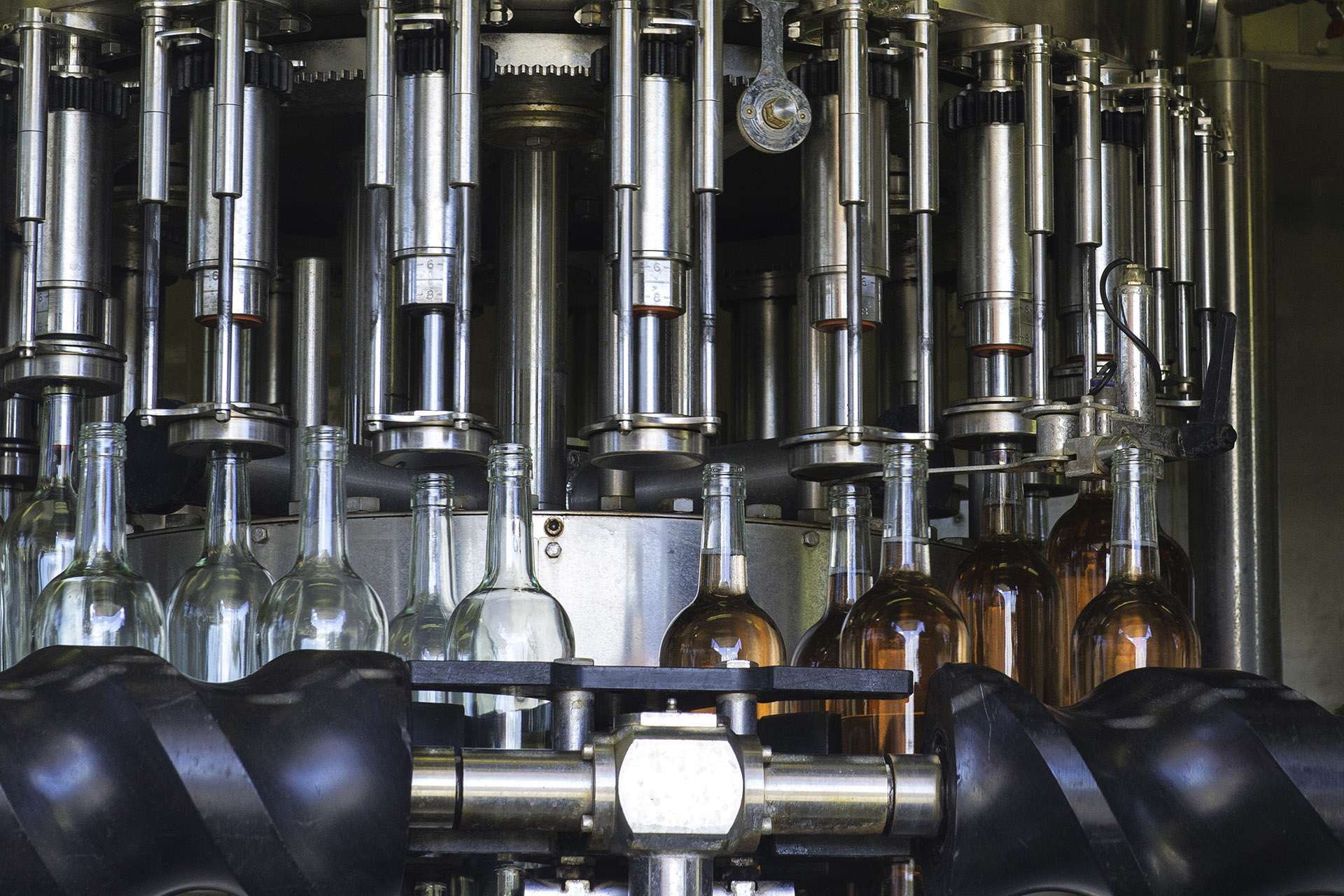 Curved machinery with empty bottles to the left and full bottles to the right