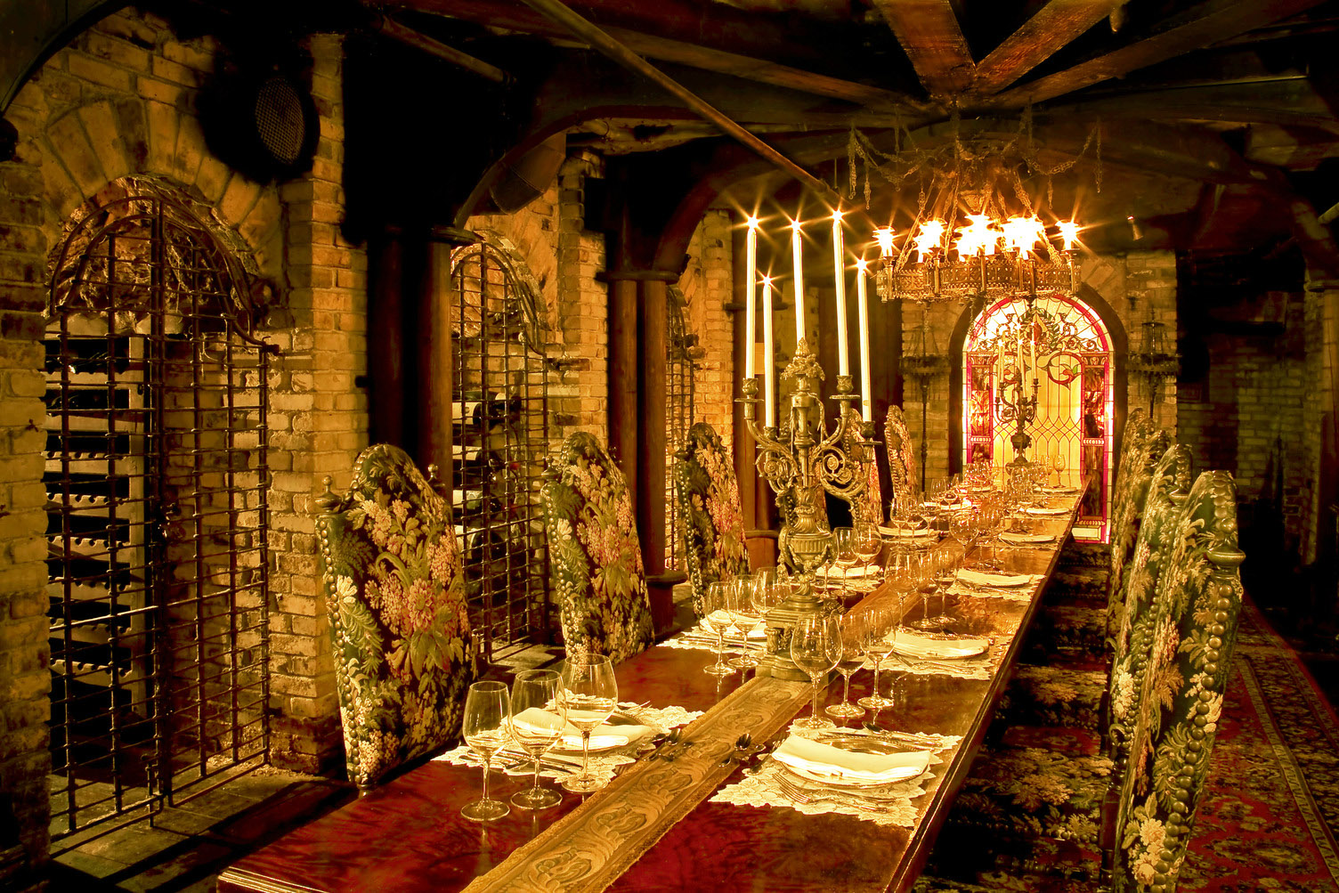 A Gothic-inspired wine cellar with a long table in the middle, with a lit candelabra