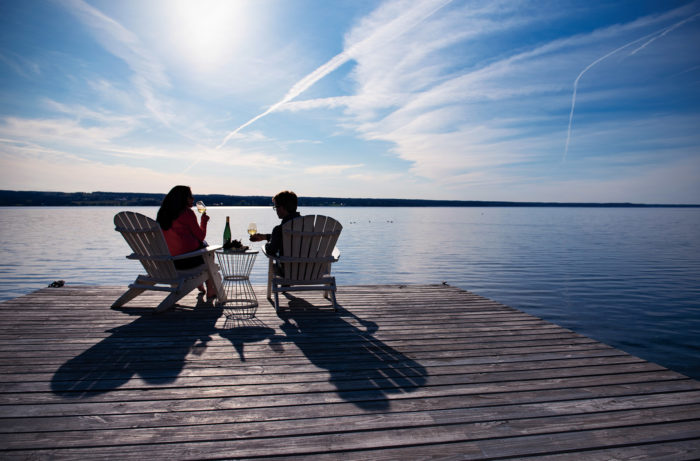 A man and a woman sipping wine in Adirondack chairs on a wooden pier in a lake