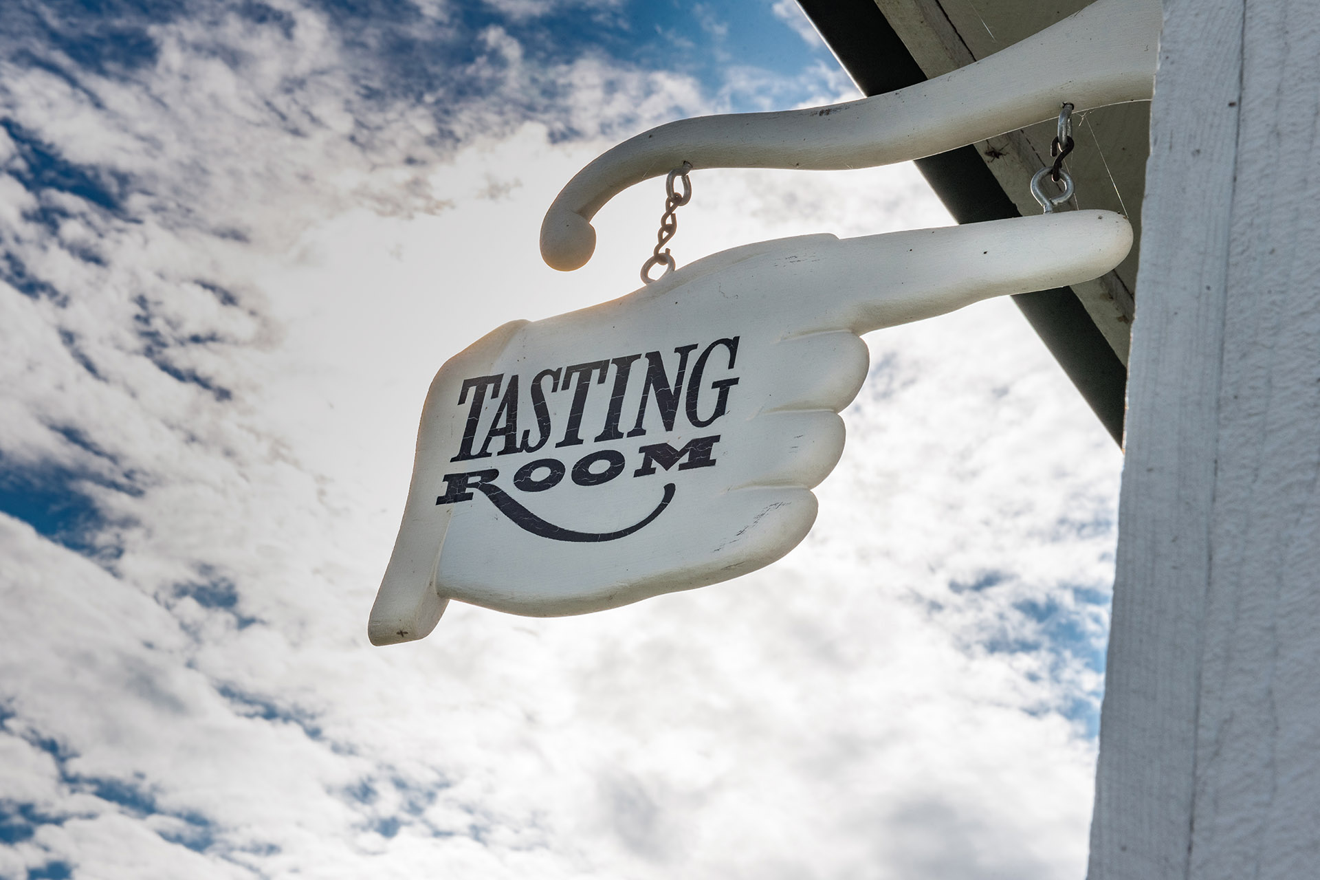 "A wooden sign saying ""Tasting Room"""