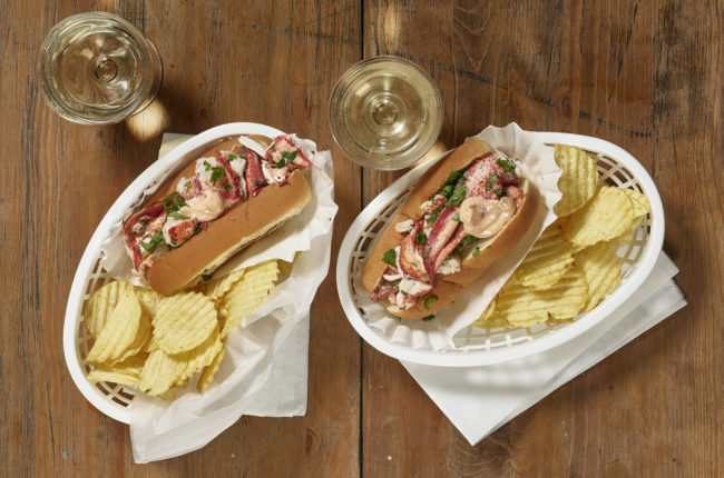 Two lobster rolls with ripples chips in white baskets