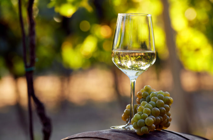 White wine grapes at the base of a wine glass holding white wine