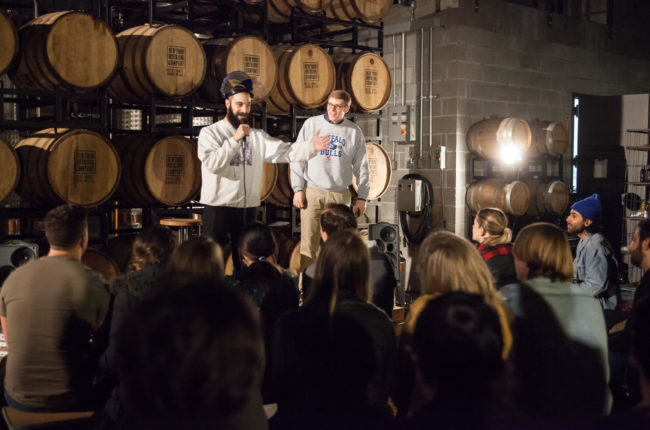 Two men in front of audience, barrels behind them