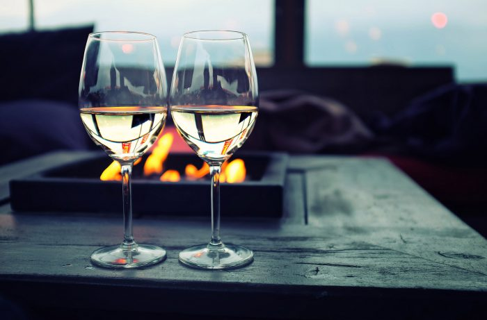 Two glasses of wine by a fire