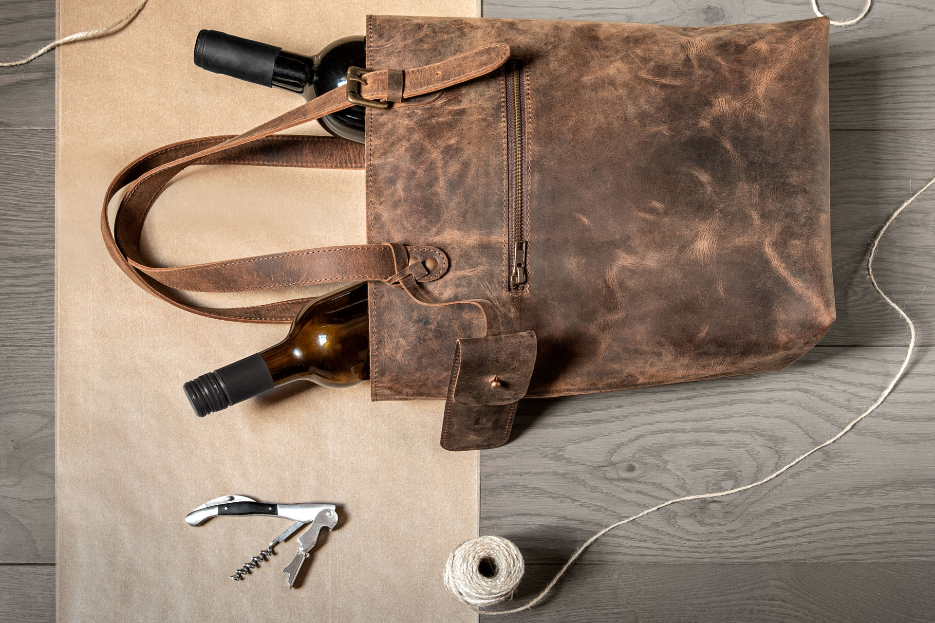 Photo of leather wine bag with two bottles in it, corkscrew to the side