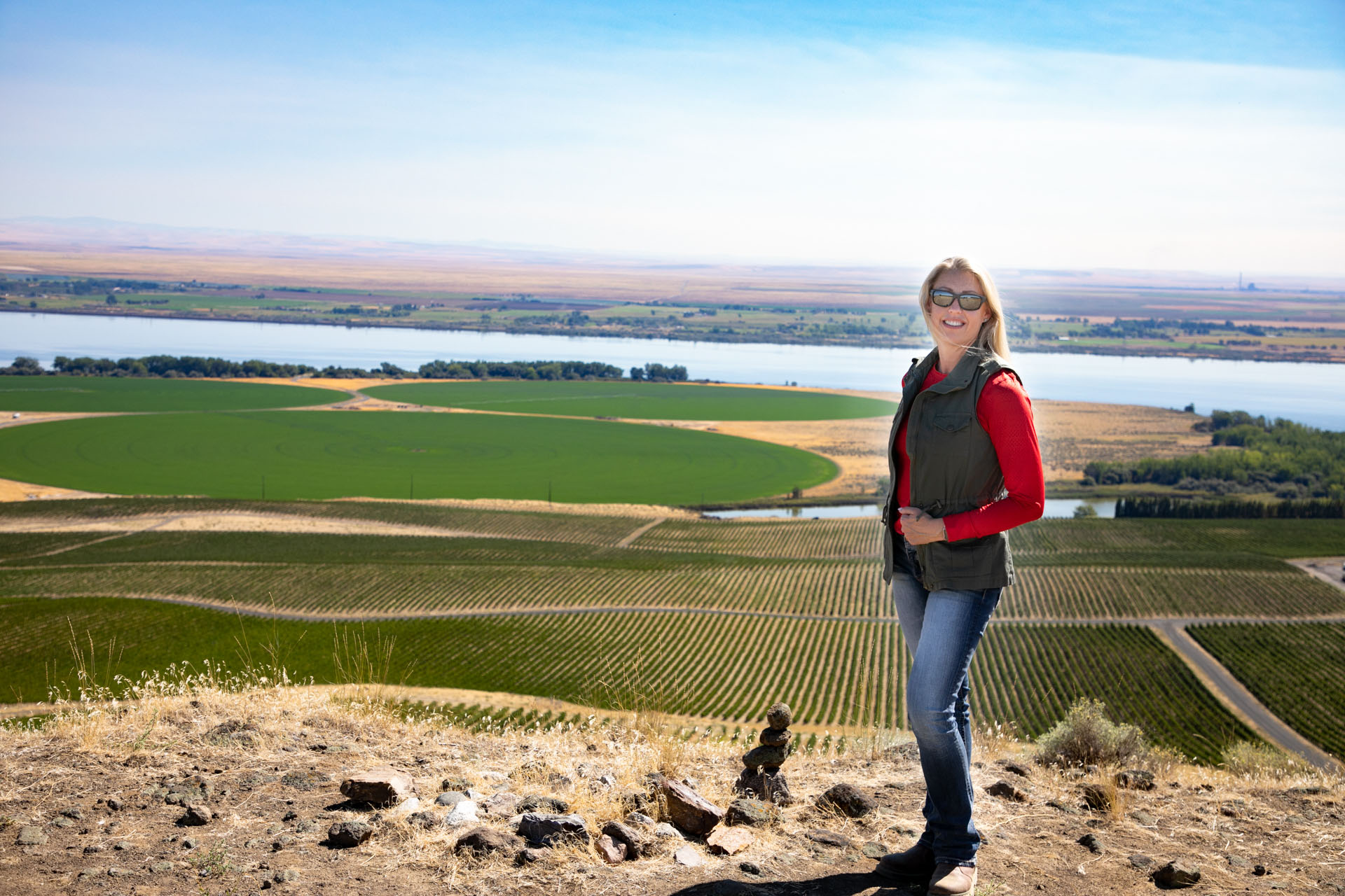 Woman standing on hill above vineyard
