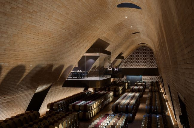 Elongated arched warehouse with barrels, a glass square in the wall to the left is the separate tasting room