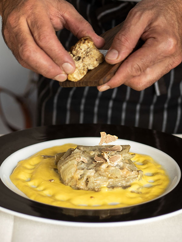 Chef shaving Alba white truffles on dish