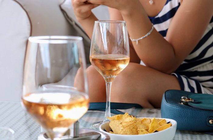 Woman eating chips and drink rosé wine