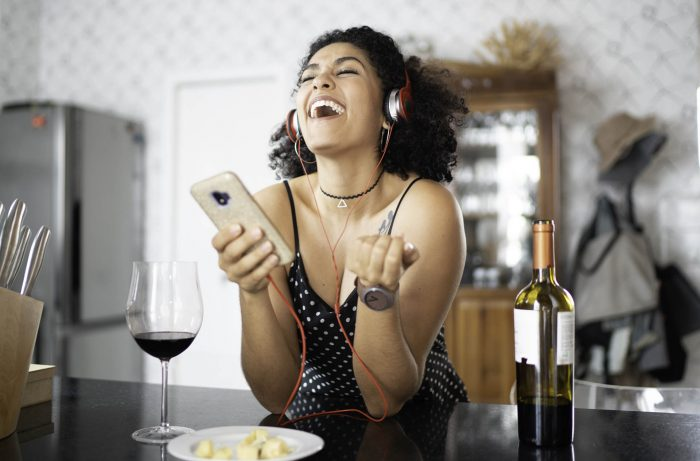 Woman Listening to a wine podcast at Home
