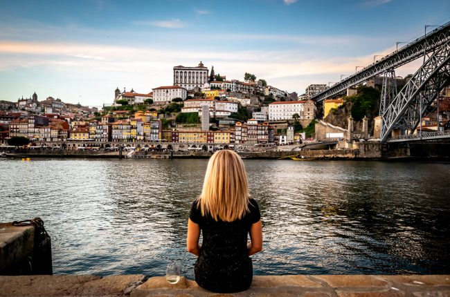 Woman looking at sunset over the Douro river in Porto with Portuguese white wine