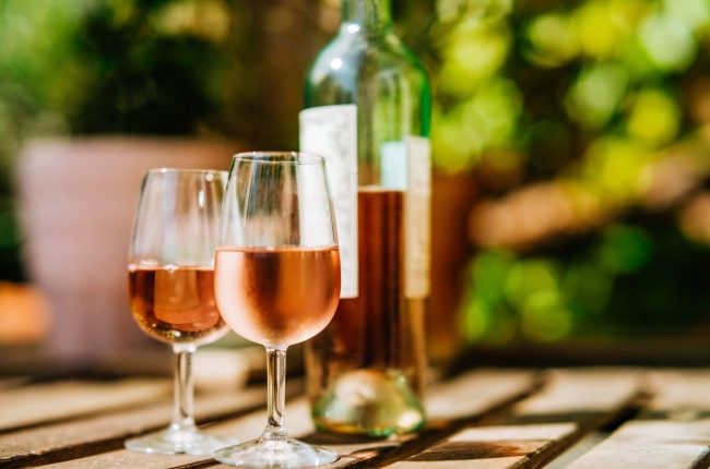 Two glass of rosé and a bottle of rosé on a table outside