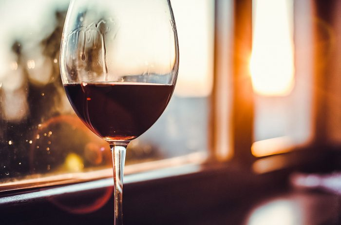 A photo of red wine near a window