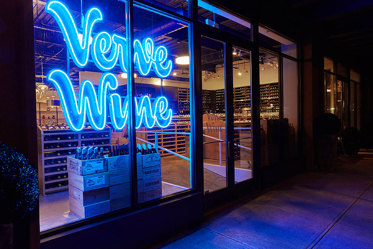 Exterior night photo of Verge Wine with blue neon sign