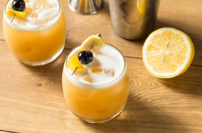 Two whiskey sours on wood table with lemon and cherry