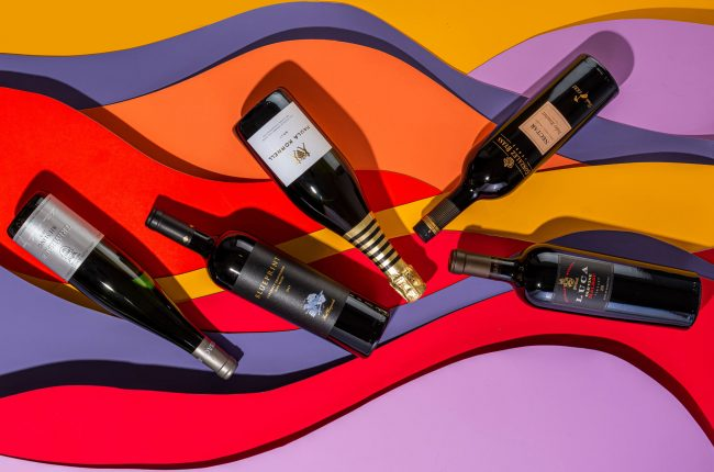 Wine bottles on multicolored background
