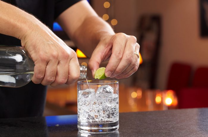 Hands squeezing lime and pouring vodka