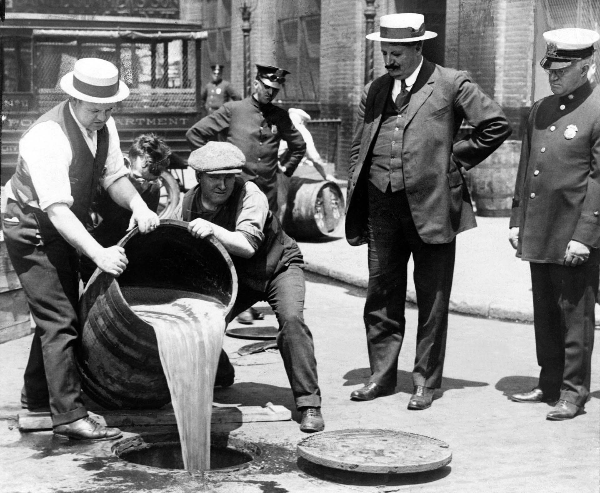 New York City Deputy Police Commissioner John A. Leach watching agents pour alcohol down a manhole following a raid during Prohibition 1921