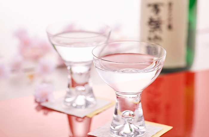 Two glasses of sake on red table