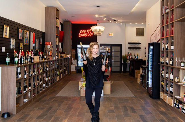 Melissa Zeman holding two bottles of wine in interior of BottlesUp