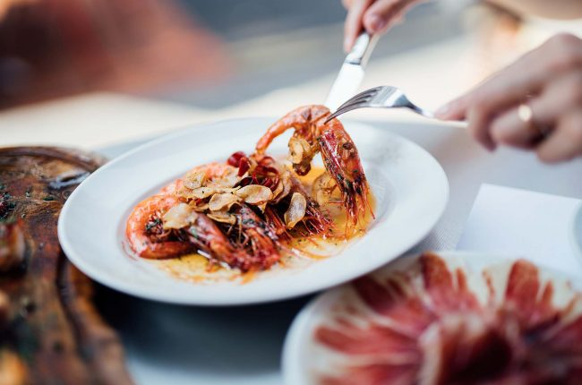 A plate of Spanish-style grilled shrimps, cooked with lemon juice, olive oil and sea salt.