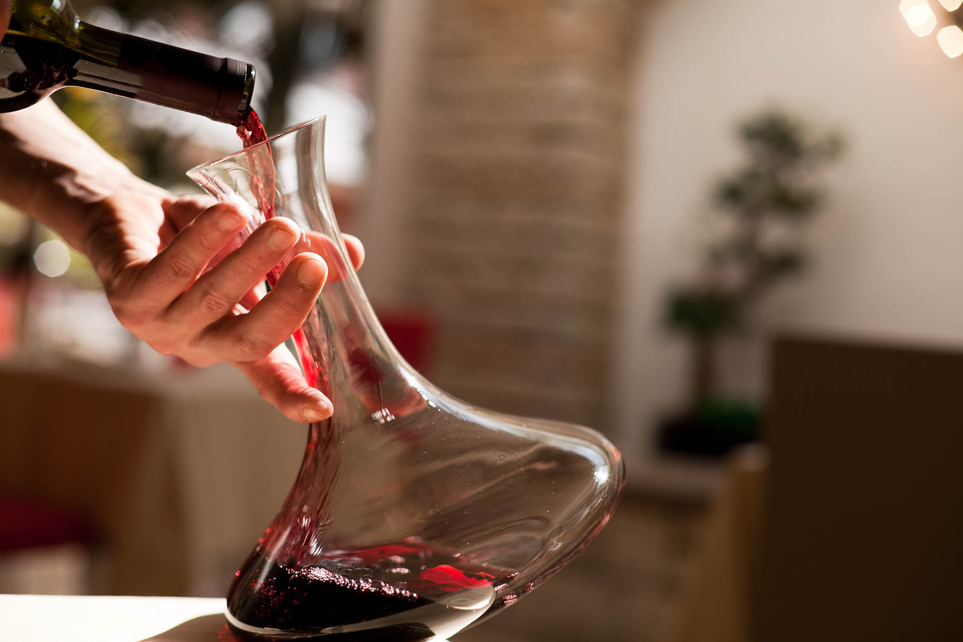 Red wine being poured into decanter