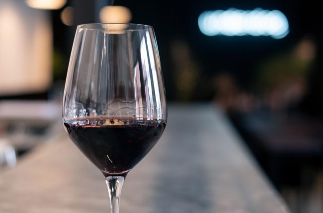 Close-up of a glass of red wine on a bar counter